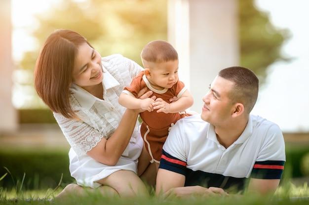 Felice giovane famiglia asiatica che trascorre del tempo all'aperto durante le vacanze estive. la giovane famiglia felice trascorre del tempo all'aperto in giardino durante le vacanze estive. famiglia felice, assicurazione sulla vita, stabilità nel concetto di vita.