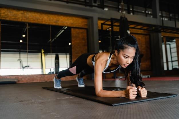 Felice giovane signora asiatica facendo allenamento bruciagrassi della plancia in lezione di fitness.