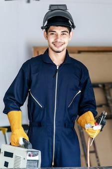 Il giovane saldatore maschio asiatico felice tiene la torcia di saldatura sul posto di lavoro. officina e concetto di sicurezza della costruzione.