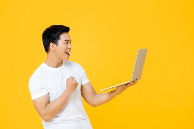 Giovane uomo asiatico felice che esamina computer portatile e che alza il suo pugno che fa gesto di sì isolato sulla parete gialla