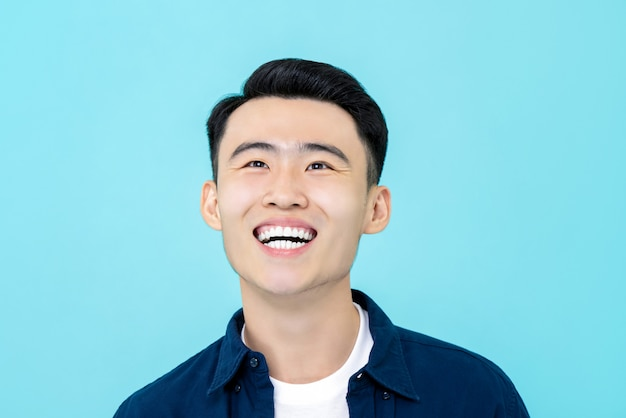 Giovane uomo asiatico felice che sorride e che guarda verso l'alto