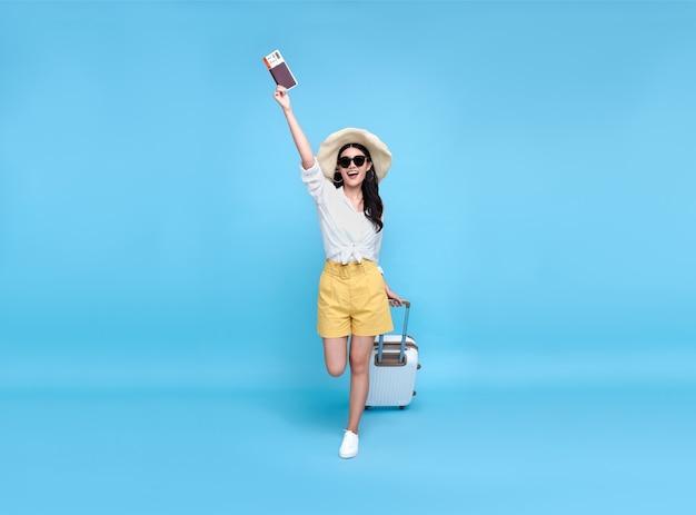 Felice giovane turista asiatico donna in possesso di passaporto e carta d'imbarco con bagagli che vanno a viaggiare in vacanza isolato su sfondo blu.