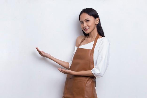 Felice giovane donna asiatica barista cameriera che punta con le dita in direzioni diverse