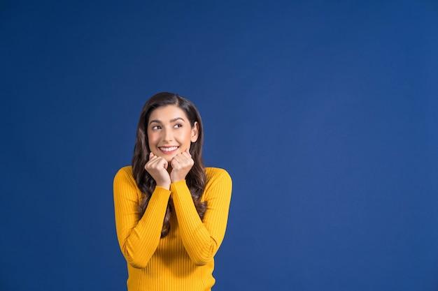 Felice giovane donna asiatica in abiti casual colorati di colore giallo eccitante e alla ricerca