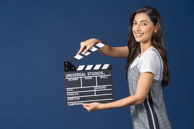 Felice giovane donna asiatica che tiene il ciak del film sul film di installazione dello studio