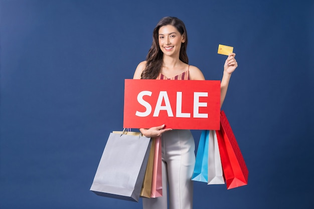 Felice giovane donna asiatica tenendo la bandiera di vendita e presentando la carta di credito per lo shopping online su sfondo di colore blu