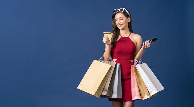 Felice giovane donna asiatica alla ricerca di carta di credito e utilizzando il telefono cellulare per lo shopping online su sfondo di colore blu