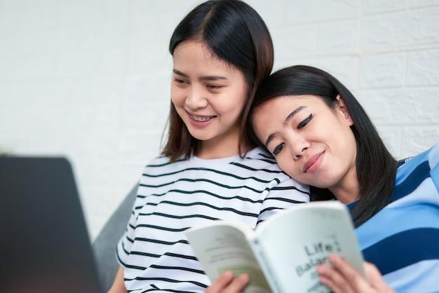 Felice giovane donna asiatica seduta sul divano e leggere il libro nel suo soggiorno, tempo di vacanza.