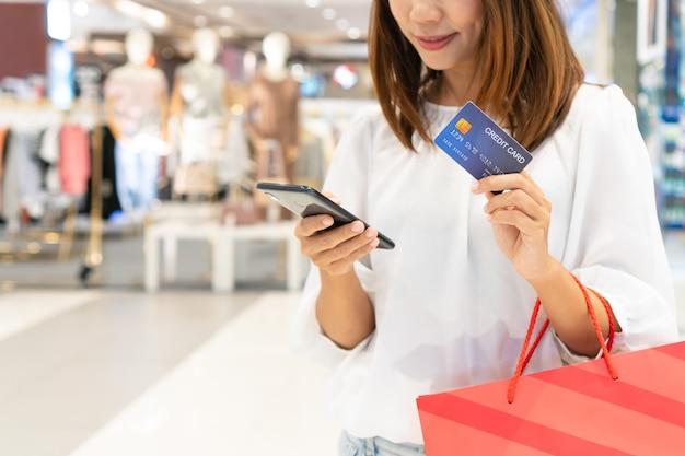Felice giovane donna asiatica utilizzando il telefono cellulare