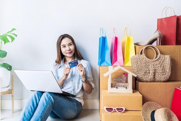 Felice giovane donna asiatica con borsa della spesa colorata, articoli di moda e pila di scatole di cartone a casa, utilizzando la carta di credito per il concetto di shopping online