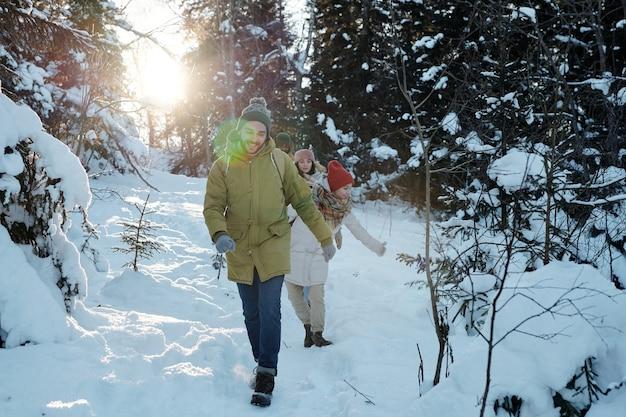 Giovani backpackers felici che si spostano verso il basso il cumulo di neve nella foresta
