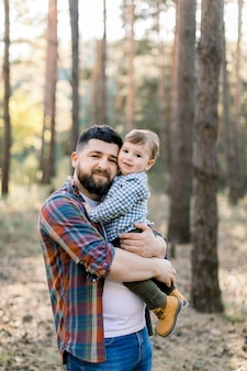 Felice giovane barbuto papà che tiene suo figlio, ragazzino divertente ragazzino, guardando la fotocamera mentre si cammina insieme in un parco o foresta al giorno pieno di sole