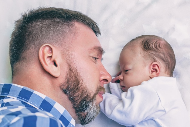 Felice giovane padre barbuto con neonato sdraiato a letto faccia a faccia, concetto di genitorialità, festa del papà
