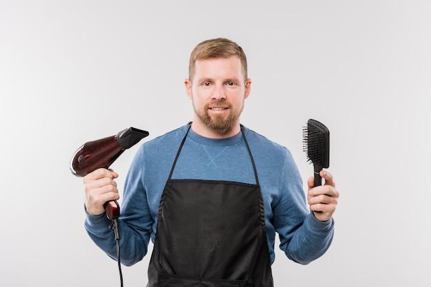 Felice giovane parrucchiere barbuto in grembiule tenendo asciugacapelli e spazzola per capelli mentre in piedi davanti alla telecamera in isolamento