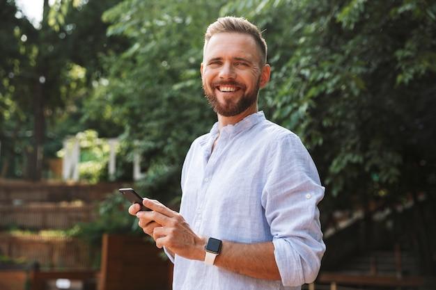 Felice giovane uomo barbuto all'aperto utilizzando il telefono cellulare.