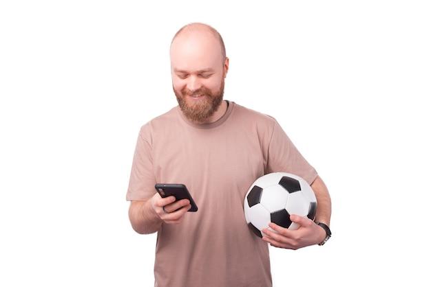 Felice giovane uomo barbuto utilizza lo smartphone e tenendo il pallone da calcio