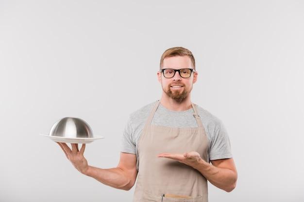 Felice giovane barbuto cameriere in grembiule e occhiali da vista che mostra cloche con cibo cotto mentre in piedi davanti alla telecamera in isolamento
