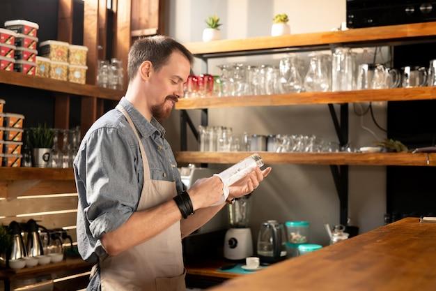 Felice giovane barbuto cameriere in grembiule che pulisce il vetro con un tovagliolo o un asciugamano