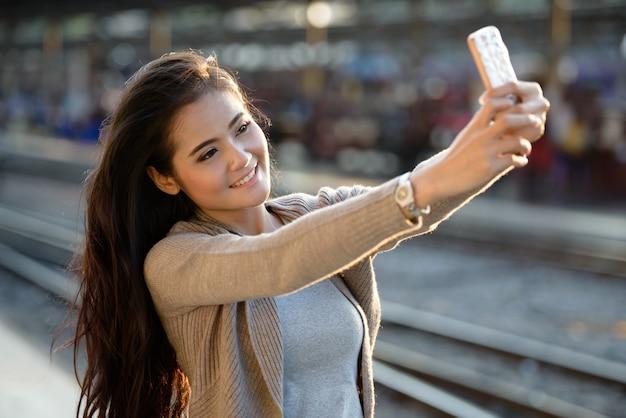 Felice giovane bella donna asiatica prendendo selfie alla stazione ferroviaria