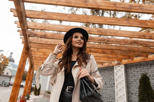 Felice giovane bella donna riccia modello con un sorriso carino in abiti alla moda con un cappotto beige elegante, cappello e borsetta cammina per strada. stile femminile ed elegante, moda e bellezza