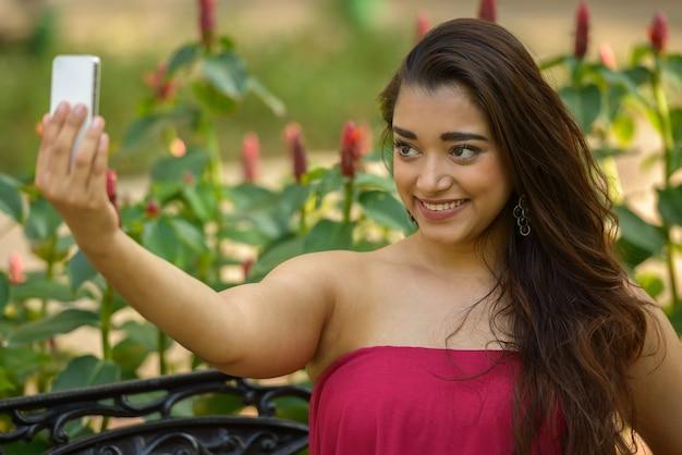 Felice giovane bella donna indiana prendendo selfie al parco