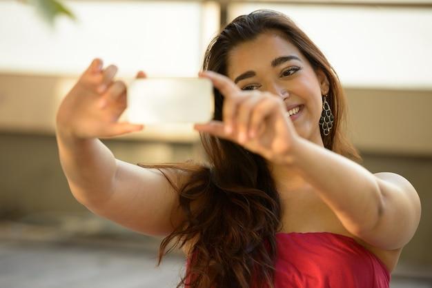 Felice giovane bella donna indiana prendendo selfie mentre è seduto sul pavimento di legno