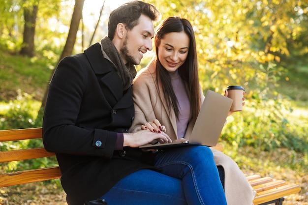 Felice giovane bella coppia di innamorati in posa a piedi all'aperto nella natura del parco seduto sulla panchina utilizzando il computer portatile.