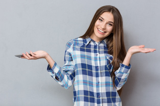 Felice giovane bella donna sorridente con i capelli kong in camicia a quadri con telefono cellulare e copyspace sui palmi