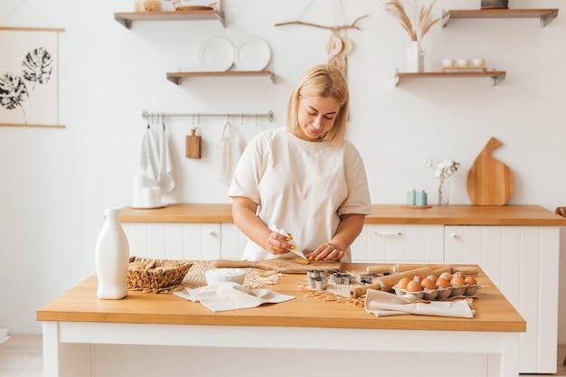 Il panettiere felice della casalinga della giovane bella donna decora i biscotti con la glassa di zucchero