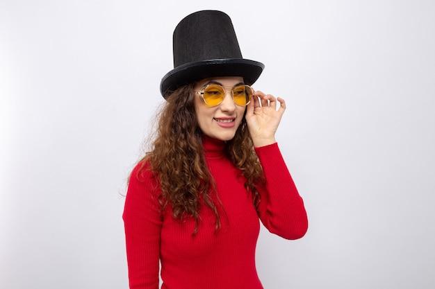 Felice giovane bella donna in dolcevita rosso con cappello a cilindro che indossa occhiali gialli che guarda da parte sorridendo allegramente in piedi su bianco