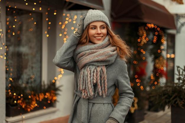 Felice giovane bella donna in un cappotto grigio alla moda con un cappello invernale lavorato a maglia alla moda e un'elegante sciarpa in un giorno di natale camminando in città vicino alle ghirlande