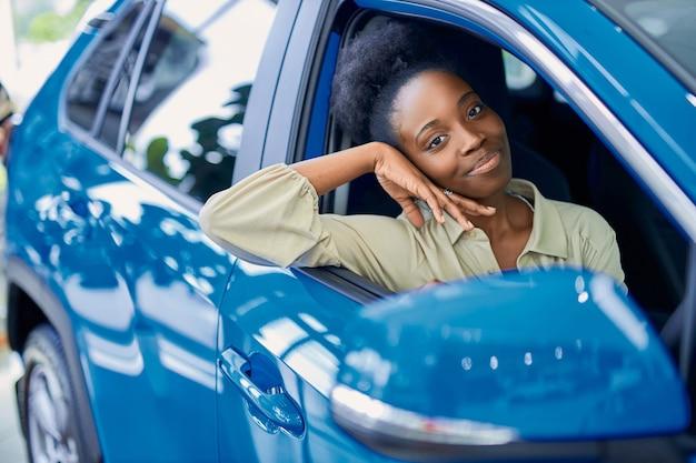 Felice giovane donna di colore in concessionaria