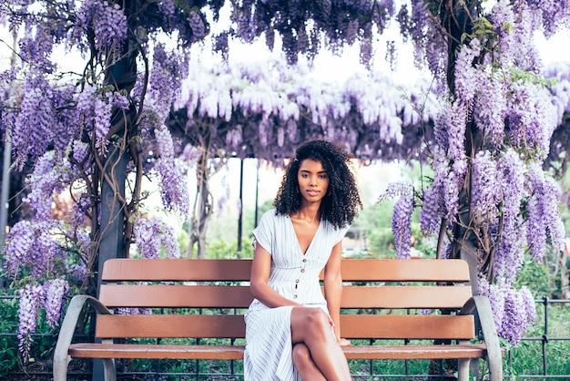 Giovane seduta felice della donna di colore circondata dai fiori