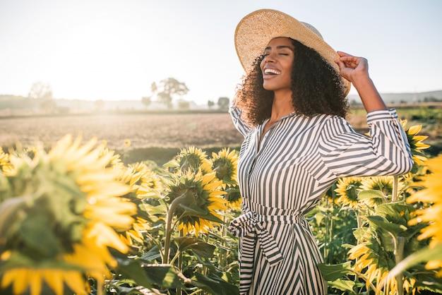 Giovane donna di colore felice in un giacimento del girasole