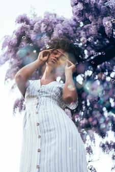 Giovane donna di colore felice circondata dai fiori