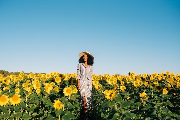 Giovane donna di colore felice che cammina in un giacimento del girasole