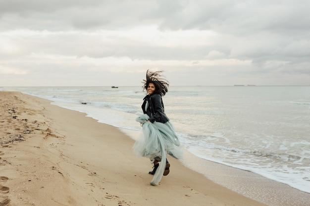 Felice giovane sposa in abito blu in esecuzione, divertirsi sulle onde pulite della spiaggia sabbiosa del mare azzurro o dell'oceano.
