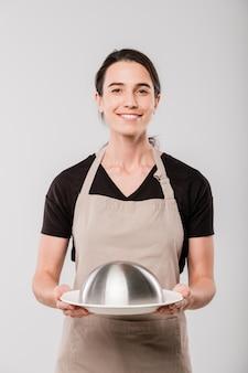 Felice giovane bruna cameriera in grembiule che tiene cloche con cibo preparato per il cliente in piedi davanti alla telecamera in isolamento