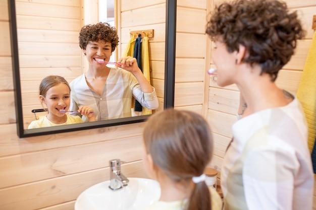 Felice giovane donna bruna e la sua graziosa figlia che si lavano i denti insieme davanti allo specchio in bagno durante l'igiene mattutina