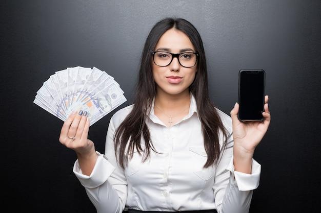 Felice giovane donna bruna in camicia bianca che mostra smartphone con schermo vuoto e denaro contante in mani isolate sulla parete nera