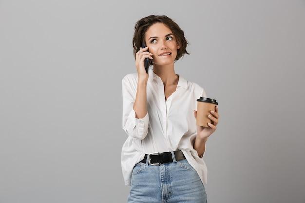 Felice giovane donna d'affari in posa isolato sopra il muro grigio parlando dal telefono cellulare e bere caffè