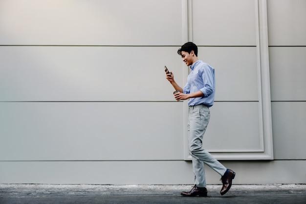 Giovane uomo d'affari felice nell'abbigliamento casual facendo uso del telefono cellulare mentre camminando dalla parete urbana della costruzione. stile di vita delle persone moderne.