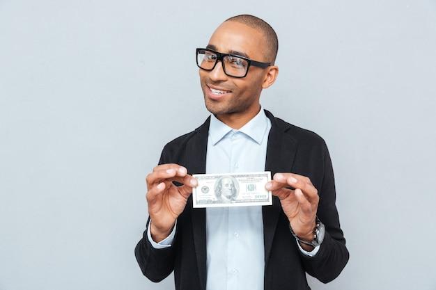 Felice giovane uomo d'affari con gli occhiali che sorride e tiene in mano una banconota in dollari