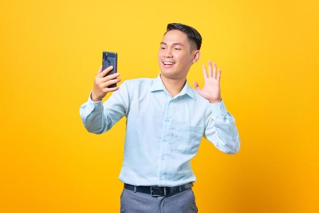 Felice giovane uomo d'affari che fa una videochiamata e agita una mano alla fotocamera dello smartphone su sfondo giallo