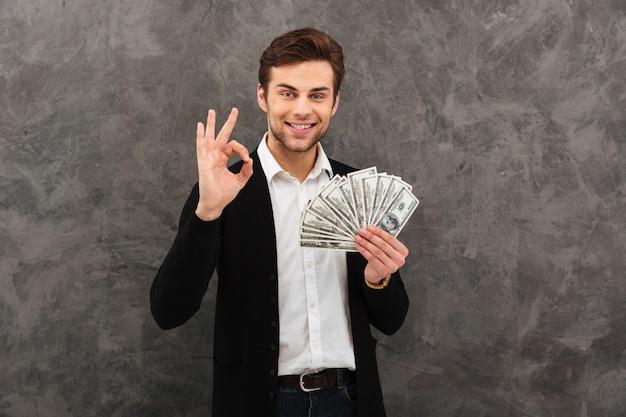 Giovani soldi felici della tenuta dell'uomo d'affari che mostrano gesto giusto.