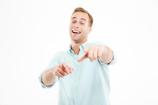 Felice giovane uomo d'affari che ride e indica te