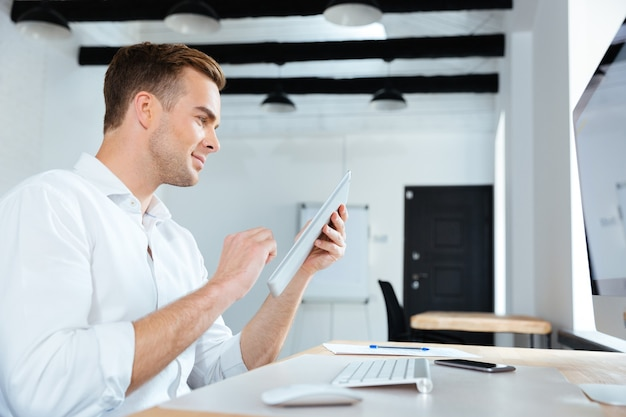 Felice giovane imprenditore seduto e utilizzando tablet in office