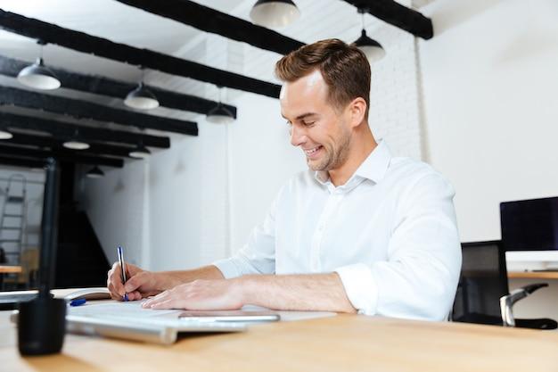 Felice giovane uomo d'affari che sorride e scrive a tavola