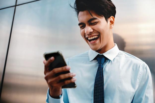 Giovane uomo d'affari felice facendo uso del telefono cellulare nella città urbana. stile di vita delle persone moderne. vista frontale. in piedi vicino al muro.