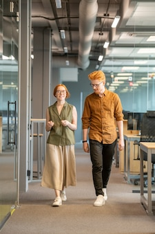 Felice giovane imprenditrice in abbigliamento casual e il suo bel collega camminando lungo il corridoio lungo la fila di scrivanie e discutendo di lavoro